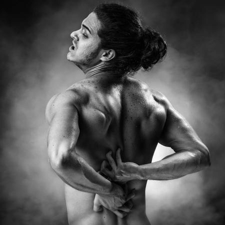 sauna nackt: Junge Sportler, die eine schmerzhafte Zucken auf Dampf Hintergrund hat Lizenzfreie Bilder