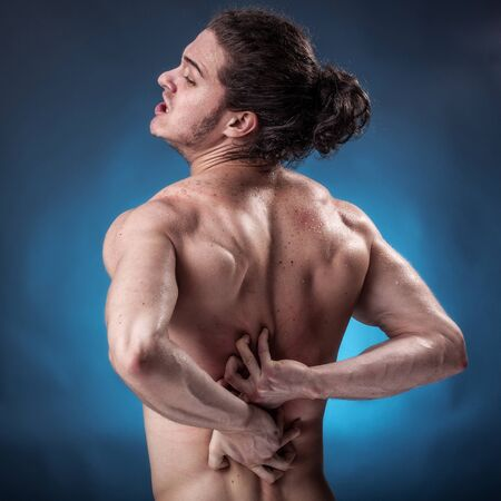 Young athlete who has a painful twinge on blue background photo