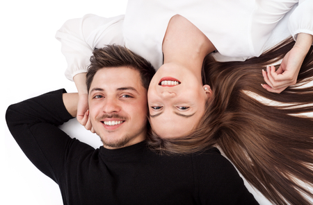 Happy young couple lying down on their back together