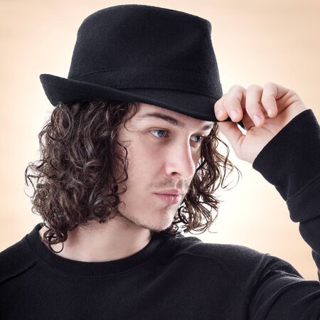 Portrait of young handsome man greet someone with hat photo