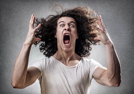 Jonge kerel geconfronteerd met een mentale instorting met een wanhopige uitdrukking Stockfoto