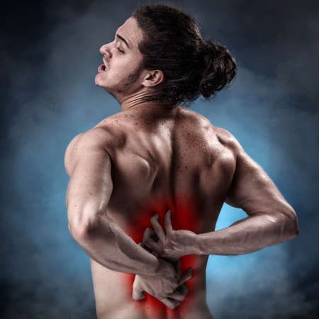 lower back pain: Handsome young man with lower back pain colored in red Stock Photo