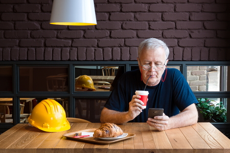 tomando refresco: maestro de obra mayor que toma refrigerio, el consumo de caf� y la comprobaci�n de su tel�fono