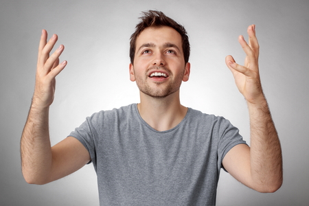 Young man looking up and worship God with raised hands Stock Photo