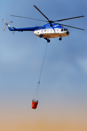 rescue helicopter: Blue fire rescue helicopter, with water bucket transportation
