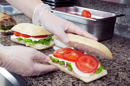 Chefs hands prepare sandwiches in a commercial kitchen