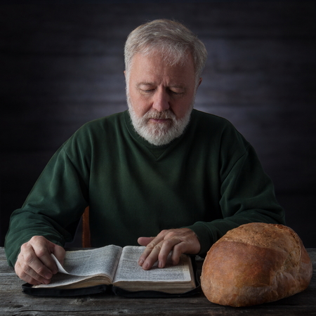 Senior pastor meditating and feeding on the Word of God not only with the daily bread next to him. Mat.4.4 Man shall not live by bread alone, but by every word that proceedeth out of the mouth of God photo