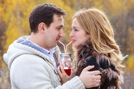 Happy young couple drinking red tea from the same pot photo