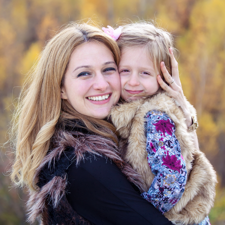 Happy mother hug her daughter in autumn background photo