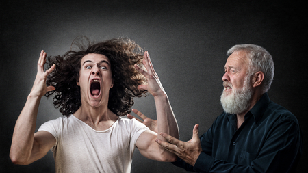 freaked: Senior looking to calm down an angry young man, son, student. Concept for angry prodigal son. Stock Photo
