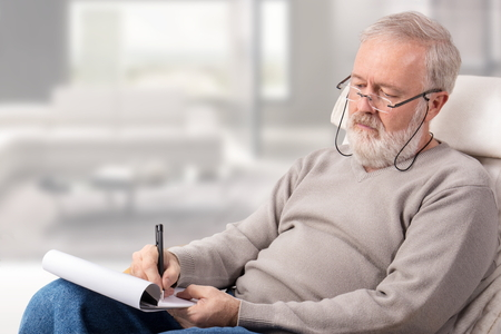 Old man making a shopping list with a pen on paper for holidays
