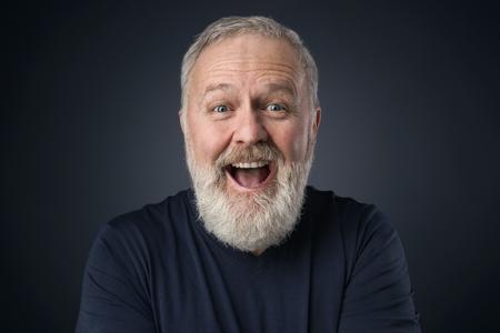 暗い背景にひげを持つ古い幸せな男