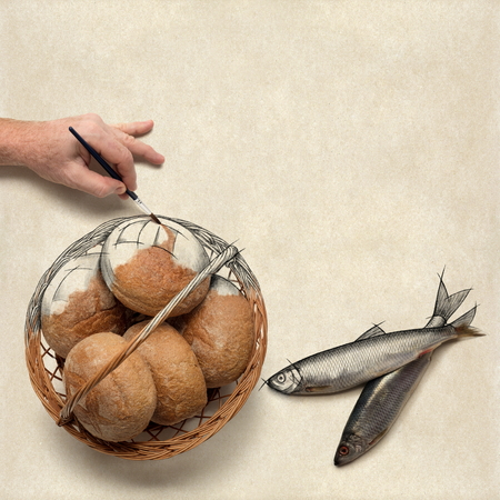 Hand painting over a drawing of five loaves of bread and two fish. Christian concept about preparing a bible study or a message on this. Фото со стока