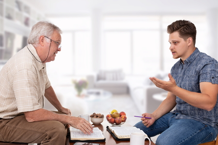 Church servant counselor doing spiritual counseling to a young man studying the Bible