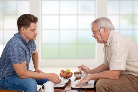 Church servant doing spiritual counseling to a young man studying the Bible Stock Photo