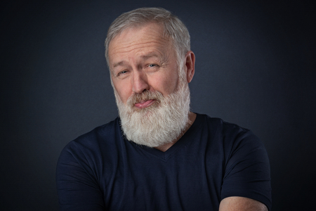 Old man with gray beard posing a despise grimace in studio