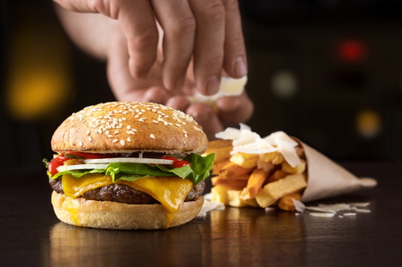 Hand that arranges beef burger with fried potatoes and cheese Banco de Imagens