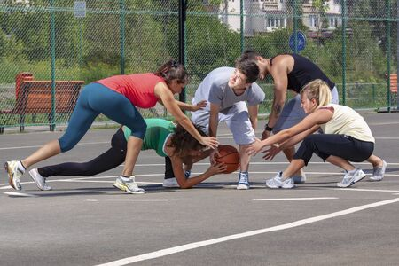 Mixed young people, men and women, playing basketball on a playground