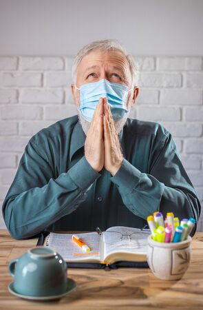 Man wearing medical mask on his face, before the Holy Bible and a cup turned on his back, concept representing prayer and fasting for viruses protection Standard-Bild