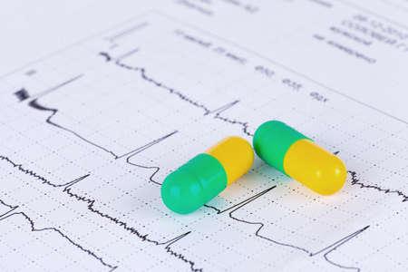 Macro of pills lying on ECG diagram photo