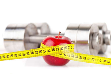 Dumbbells with an apple on a white background