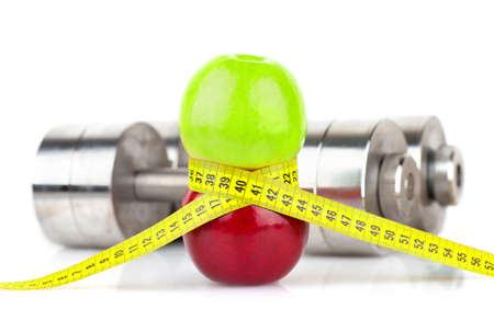 Photo of green and red apple tied with measuring tape on the background of metallic dumbbells