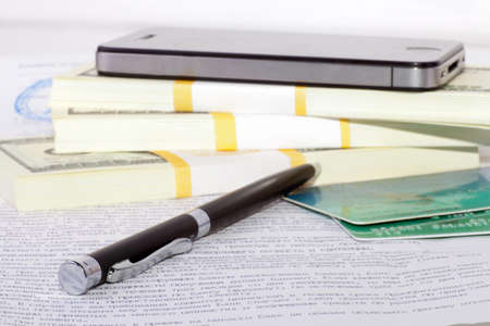 Pen, mobile phone, credit cards and heap of dollars  Financial background Stock Photo - 15789221