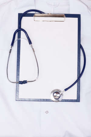Medical clipboard and stethoscope on medical gown photo