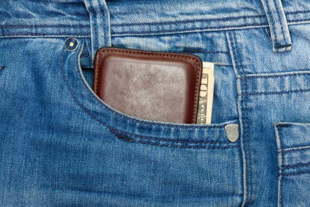 Wallet with dollars in blue jeans pocket