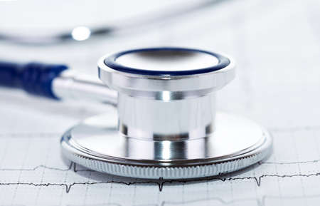 Closeup of stethoscope on ecg diagram background