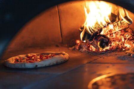 Pizza is baked in the oven near the burning wood. Neapolitan pizza