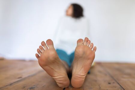 Women's feet in the foreground.The girl is sitting on a wooden floor on a white background