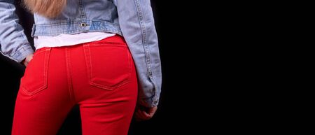 Women's in red denim trousers close-up, isolated on a black background