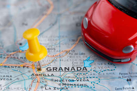 Granada city on the map. A red car as a symbol of travel