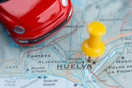 Huelva city on the map. A car as a symbol of travel