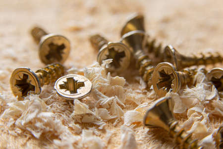 Close up wood threaded lag screw and two hand screwdrivers