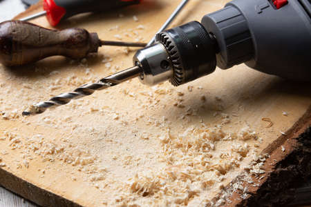 drill perched on a wooden board with shavings and other tools around