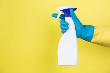 A hand with cleaning gloves squeezing a spray bottle on a yellow background