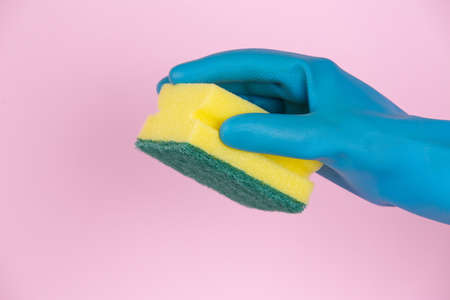 A hand with cleaning gloves holding scouring pad on pink background