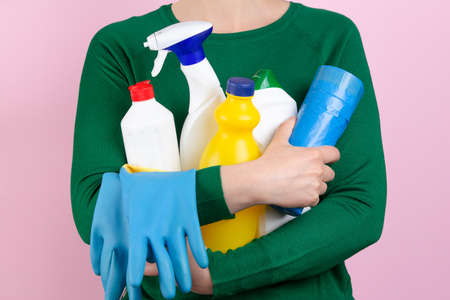woman with green sweater and pink background hugging many cleaning products in her arms Foto de archivo