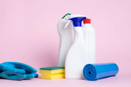 Three cans of cleaning spray with a scouring pad, globes and garbage bags placed on a pink background Banco de Imagens