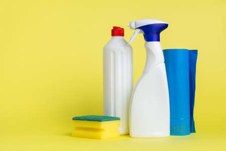 Two cans of cleaning spray with a scouring pad and garbage bags placed on a yellow background