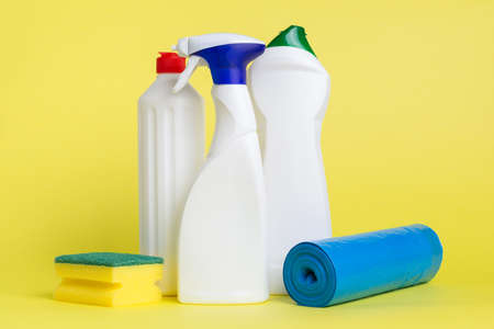 Three cans of cleaning spray with a scouring pad and garbage bags placed on a yellow background