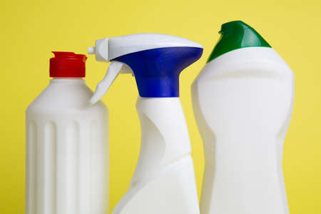 three cans of cleaning products on yellow background