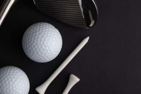 golf ball and iron stick seen very close. Black background