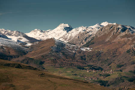 Puentenansa Valley Cantabria, with the snowy mountains. Obese town with its fortified tower on the bottom right.