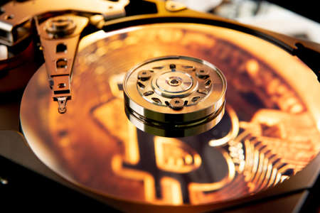 Inside of an open computer hard drive with the projected bitcoin symbol