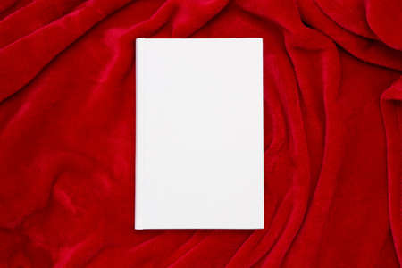 Book with blank cover and empty cover on red blanket Foto de archivo