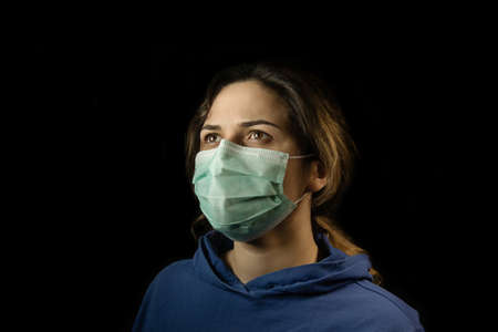 Girl in respiratory mask. Masked woman looks at camera. Cold, flu, virus, tonsillitis, respiratory disease, quarantine, epidemic concept. Stock Photo