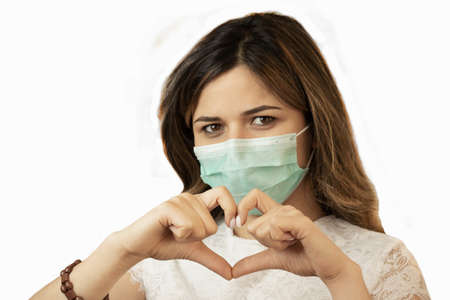 Woman with a medical mask shows the symbol of the heart. Doctor for the heart. Love our medical.